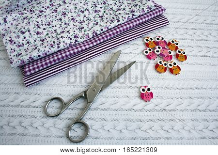 Materials for sewing - cloth , scissors and buttons on the table.  Copy space.