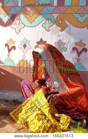 GUJARAT, INDIA - DECEMBER 20, 2013: Tribal woman practising embroidery in front of her house (Bhunga) in a local village near Bhuj