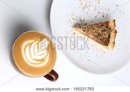Cup Of Cappuccino And A Piece Of Cake. Latte Art. Isolated On White. Top View