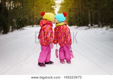 two girls kissing on a snowy road in the woods