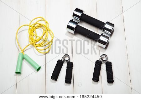 Dumbbells, a skipping rope and the expander on a white wooden background