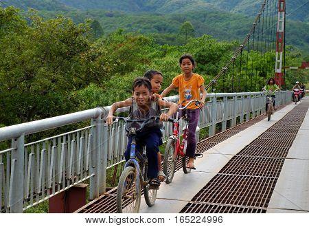 Vietnamese Children Ride Bicycle On Suspension Bridge