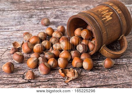 Nuts filbert, whole and peeled, in a brown wooden mug on old table.