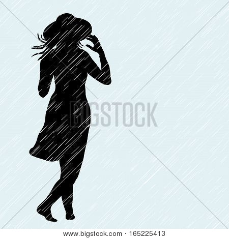 Woman with hat walking in the rain in a windy day