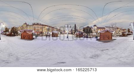 TÂRGU MUREȘ, ROMANIA - December 19, 2016: Day-night composite 360 panorama of decorated wooden booths in a snow-covered Piața Trandafirilor (Roses' Square), town centre of Târgu Mureș, Romania