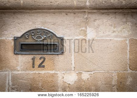 Old bronze metal letter box and house number on bricked wall