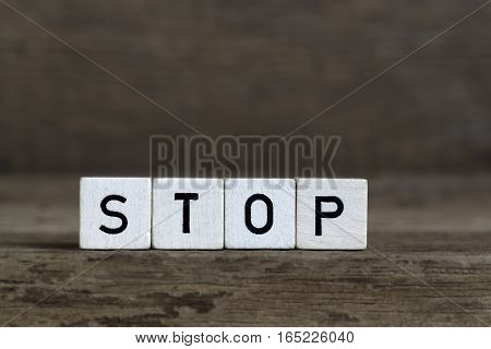 Stop written in cubes on wooden background
