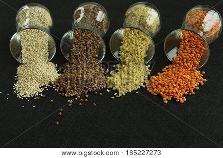 Four different groats: buckwheat lentil quinoa bulgur in transparent glasses on black background