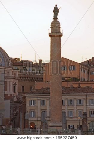 a part of Rome with the Trajan's Column and orange buildings under an evening sky