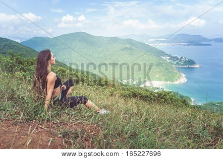 Young fitness woman in sportswear resting after exercising or running sitting on grassy mountain peak and looking at sea landscape.