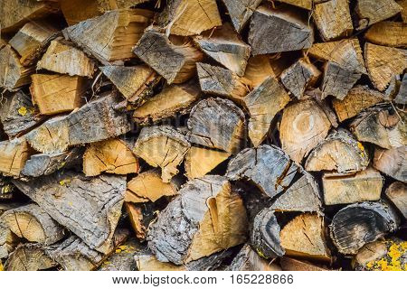 Background of firewood stacked in the cut wood timber firewood textured for background. Nature material texture brown bark cut environment pile.