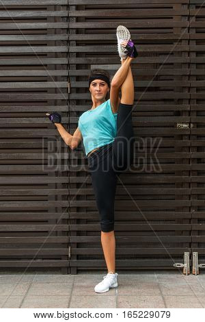 Athletic flexible young woman doing standing split exercise on the city street.