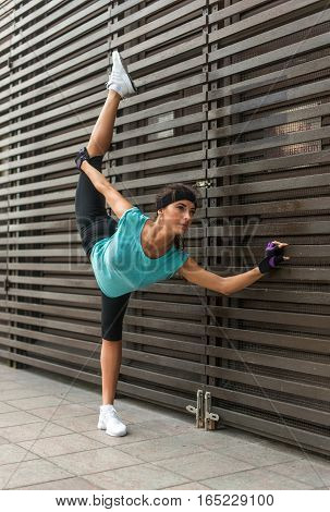 Athletic flexible young woman doing yoga standing split exercise.