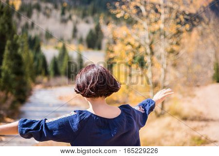 Mineral Creek stream in Colorado, USA by Silverton during the golden fall with young girl with hands in air