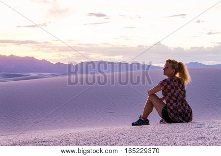 Silhouette of woman watching over White Sand Dunes during sunset