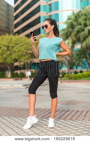 Fitness model standing, wearing sportswear and sunglasses, using phone, listening to music in headphones in city