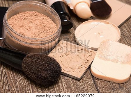 Foundation makeup products: liquid and cream foundation, concealer, powder with sponge and make up brushes. Shallow depth of field