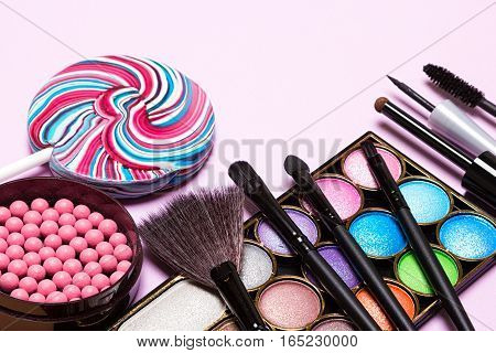 Decorative cosmetics for festive party makeup. Blush, color glitter eyeshadow, liquid eyeliner, mascara, brushes with lollipop. Copy space