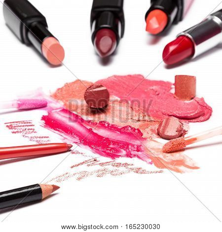 Lip make up cosmetics. Different color samples of smeared and sliced lipstick, lip gloss, lip liners on white textured surface. Shallow depth of field