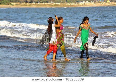 DIU, INDIA - JANUARY 6, 2014: Colorful and beautiful young women walking on the seashore in Diu Island