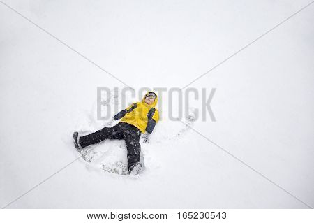 boy on a snow angel shows. winter fun. happy kid laying on snow and making snow angel. top view. empty space for your text