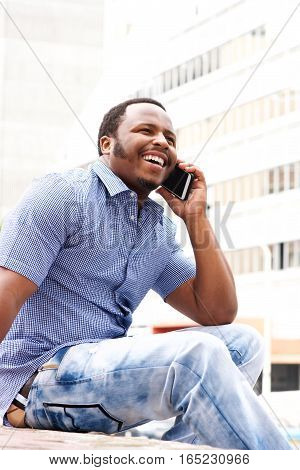 Young Man Sitting In City Talking On Cellphone
