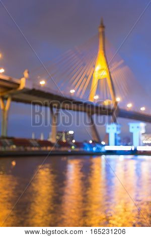 Blurred lights over Suspension bridged over watergate night view abstract background