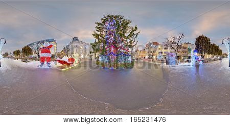 TÂRGU MUREȘ, ROMANIA - December 29, 2016: Day-night composite of a giant Christmas tree in a snow-covered Piața Trandafirilor (Roses' Square), town centre of Târgu Mureș, Romania