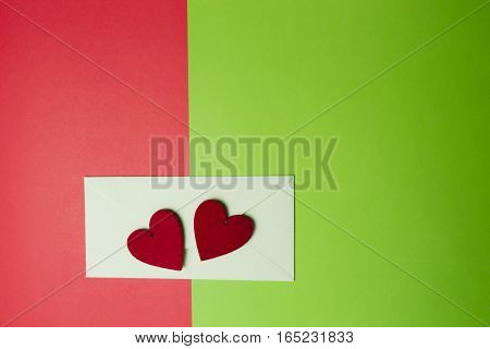 Envelop and two red hearts on greenery and red colored paper background. Top view. Flat lay. Copy space for text