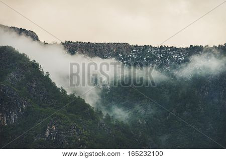 Green slopes of the Taurus mountains covered with snow and clouds in winter. Southern Turkey, Alanya, Dim Cay river valley