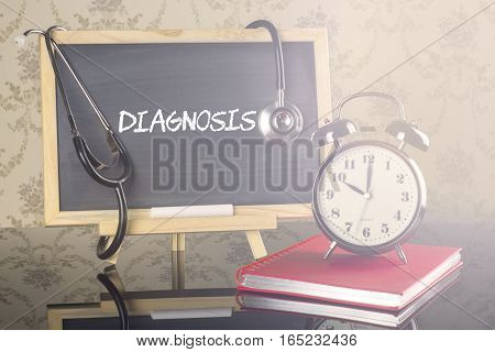 Diagnosis on blackboard with stethoscope and alarm clock.