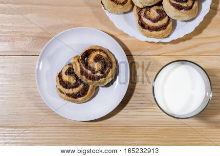 Sweet cinnamon rolls with milk on a wooden table