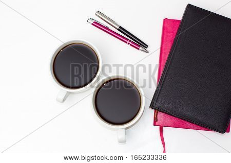 two cups of black coffee two of the diary and two pens on a white background. flat lay of the business concept of relationship men and women
