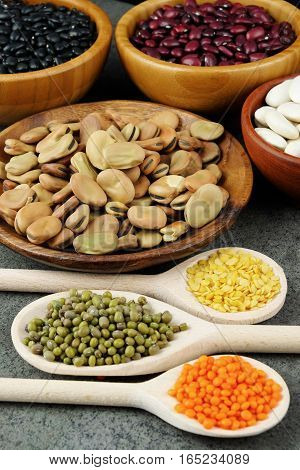 Dried black white red broad beans and and red and yellow lentils on wooden spoons and in wooden bowls on a dark rustic table.