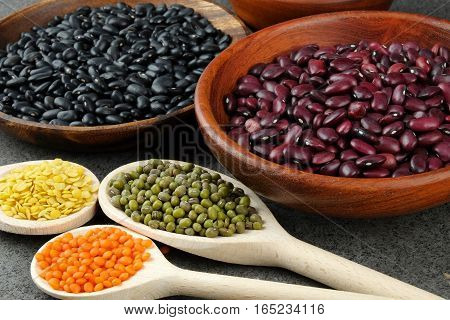 Dried black and red beans and green red and yellow lentils on wooden spoons and in wooden bowls on a dark rustic table.