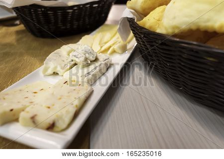 cheese plate with three different types and basket of crescentine