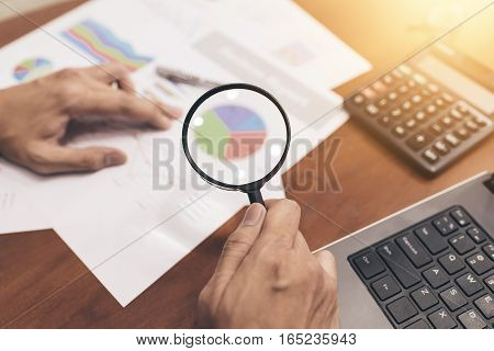 Man hand holding magnifying glass analyzing business financial data. Photo with sunlight filter effect.