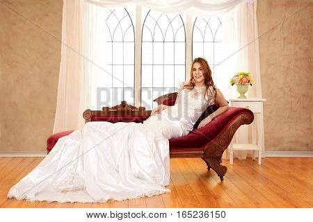 red head bride sitting on fainting couch by window