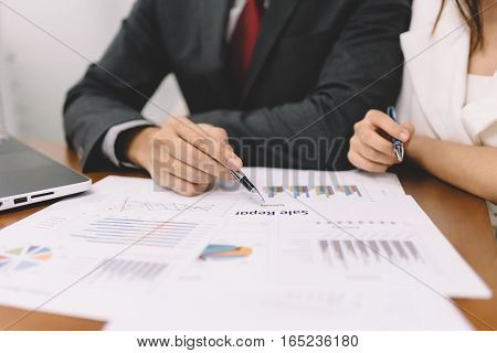 Businessman and woman discussing in business meeting with document on the table