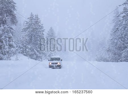 Landscape with snowfall and car on winter road