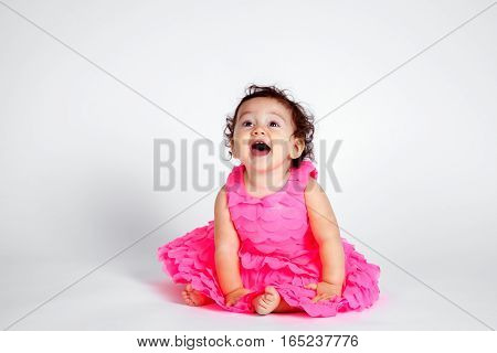 A happy Native American baby girl sits on a white background. She is wearing a pink dress and leans forward with a huge excited open mouth smile.
