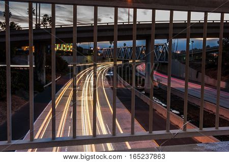Streaking northbound traffic during morning rush hour looking through iron balusters.