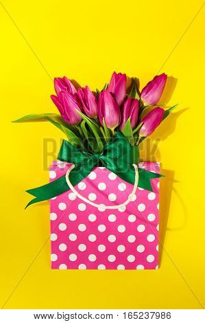 Fresh beautiful lila tulips in gift package on bright yellow background. Spring concept. Top view.