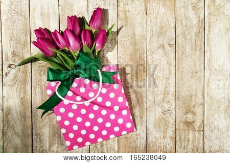 Fresh beautiful lila tulips in gift package on wooden background. Spring concept. Horizontal top view with copy space.