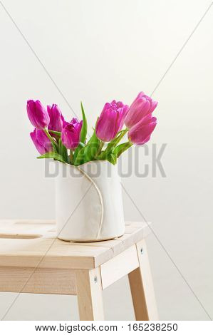 Beautiful Fresh Spring lila Tulips in Vase on Wooden Stool. Spring easter or Mother's Day Concept.