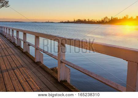 Wooden footbridge to sea at sunset. Kaivopuisto park, Helsinki, Finland.