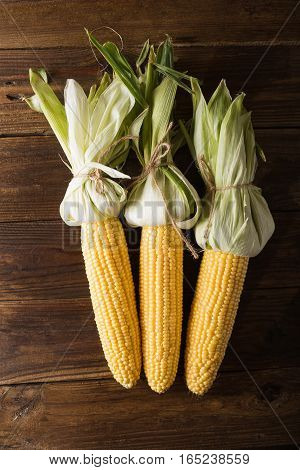 Grains of ripe corn on wooden background. Corn cob and green leaves on wooden background food Top viev Copyspace