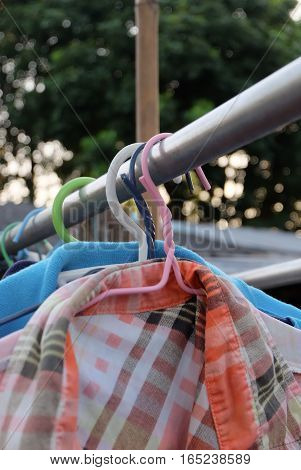 Coat hangers hanging on a clothes line.