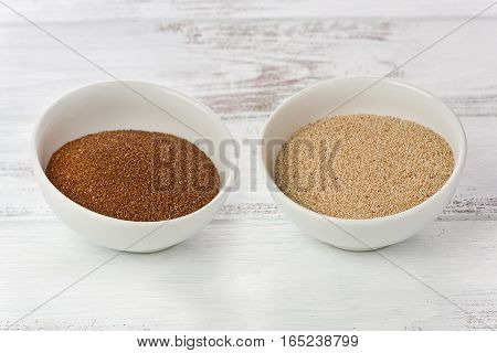Two small bowls with ethiopian teff grains on a painted wood background. One bowl has brown teff grains and the other has white teff grains.