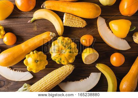 Yellow fruits and vegetables on a wooden background. Colorful festive still life. Copyspace. Yellow squash melon lemon banana pepper apples corn